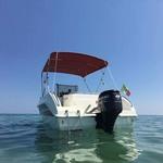 Bimini-Top Sport mit 4 Bögen in rot, montiert auf einem Sportboot mit Center Konsole (Heck)